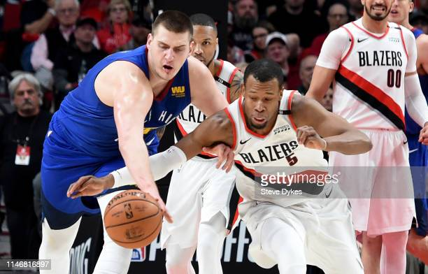 Nikola Jokic of the Denver Nuggets and Rodney Hood of the Portland Trail Blazers go after a loose ball during the first half of game three of the...
