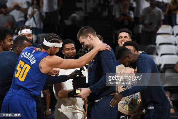 Nikola Jokic of the Denver Nuggets celebrates the Maurice Podoloff Trophy for MVP with his teammates before the game against the Phoenix Suns during...