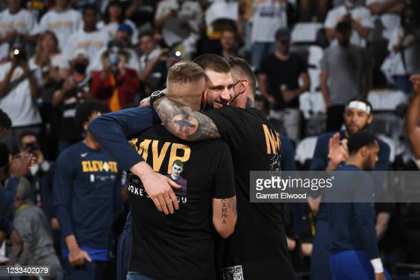 Nikola Jokic of the Denver Nuggets celebrates the Maurice Podoloff Trophy for MVP with his brothers before the game against the Phoenix Suns during...