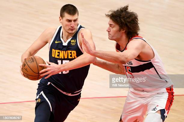 Nikola Jokic of the Denver Nuggets dribbles in front of Robin Lopez of the Washington Wizards during the first half at Capital One Arena on February...