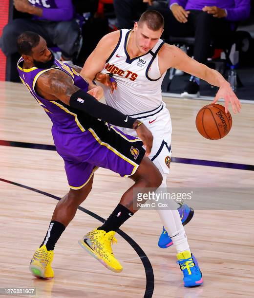 Nikola Jokic of the Denver Nuggets drives the ball against LeBron James of the Los Angeles Lakers during the third quarter in Game Five of the...