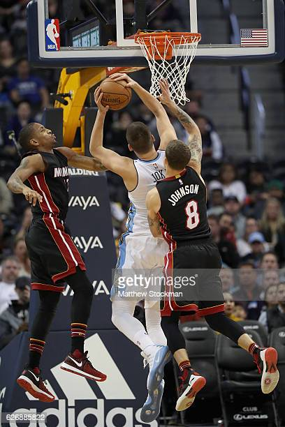 Nikola Jokic of the Denver Nuggets drives to the basket against Rodney McGruder and Tyler Johnson of the Miami Heat at the Pepsi Center on November...