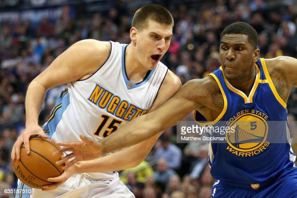 Nikola Jokic of the Denver Nuggets drives to the basket against Kevin Looney of the Golden State Warriors at the Pepsi Center on February 13 2017 in...