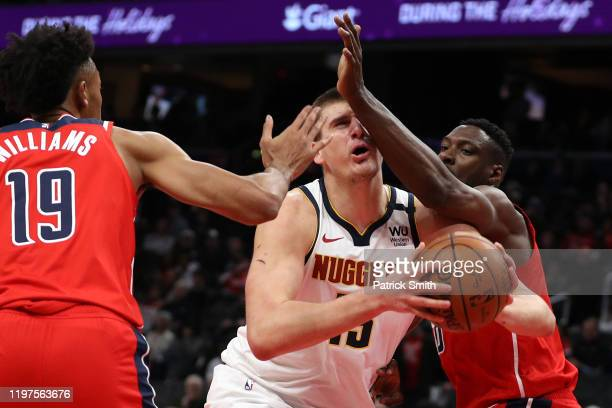 Nikola Jokic of the Denver Nuggets is fouled by Ian Mahinmi of the Washington Wizards during the first half at Capital One Arena on January 04, 2020...
