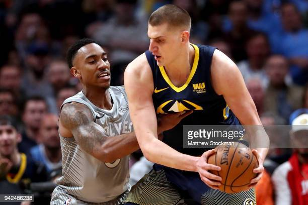 Nikola Jokic of the Denver Nuggets is guarded by Jeff Teague of the Minnesota Timberwolves at the Pepsi Center on April 5 2018 in Denver Colorado...