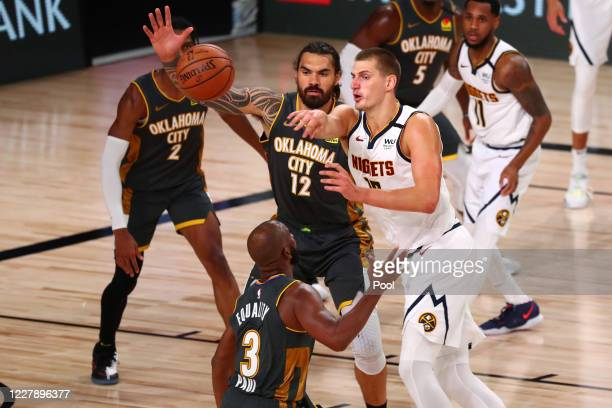 Nikola Jokic of the Denver Nuggets passes the ball against Steven Adams and Chris Paul of the Oklahoma City Thunder during third quarter at The Arena...