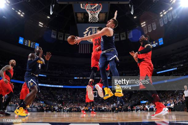 Nikola Jokic of the Denver Nuggets passes the ball in the paint against the Portland Trail Blazers during Game Seven of the Western Conference...