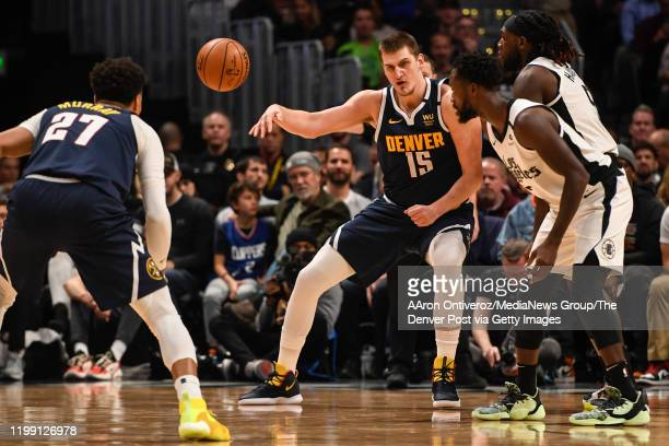 Nikola Jokic of the Denver Nuggets passes to Jamal Murray as Montrezl Harrell of the LA Clippers plays physical defense in the post during the third...