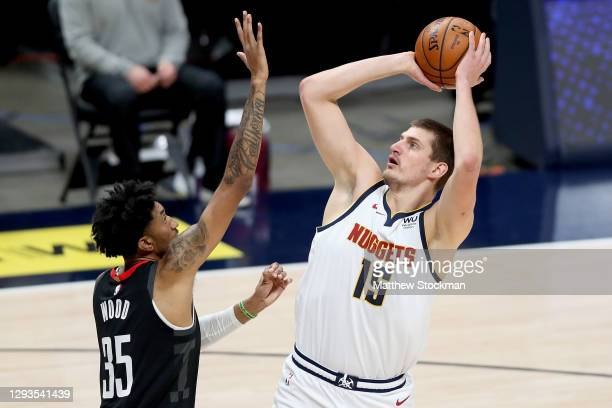 Nikola Jokic of the Denver Nuggets puts up a shot over Christian Wood of the Houston Rockets in the first quarter at Ball Arena on December 28, 2020...