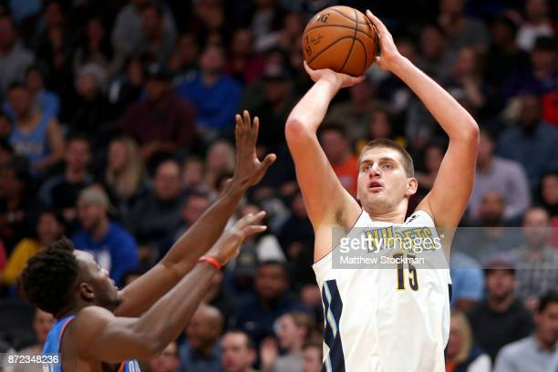 Nikola Jokic of the Denver Nuggets puts up a shot over Jemari Grant of the Oklahoma City Thunder at the Pepsi Center on November 9 2017 in Denver...