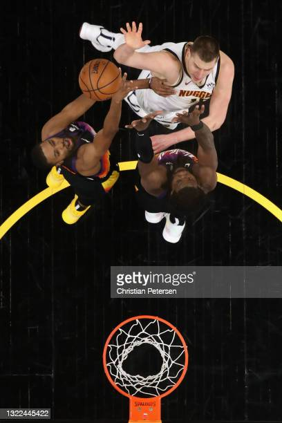 Nikola Jokic of the Denver Nuggets puts up a shot over Mikal Bridges and Deandre Ayton of the Phoenix Suns during the second half in Game One of the...
