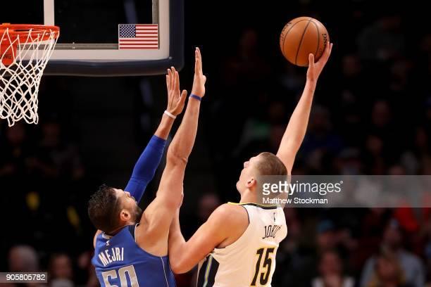 Nikola Jokic of the Denver Nuggets puts up a shot over Salah Mejri of the Dallas Mavaricks at the Pepsi Center on January 16 2018 in Denver Colorado...
