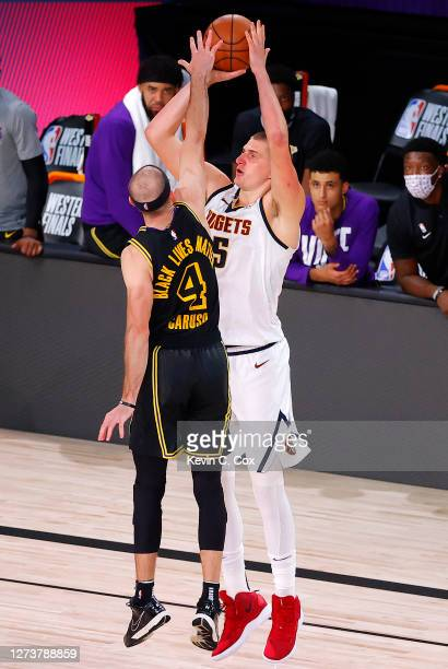 Nikola Jokic of the Denver Nuggets shoots the ball over Alex Caruso of the Los Angeles Lakers during the fourth quarter in Game Two of the Western...