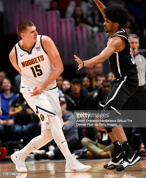 Nikola Jokic of the Denver Nuggets throws a nifty behind-the-back pass to Gary Harris as Jarrett Allen of the Brooklyn Nets defends during the first...
