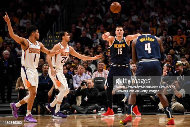 Nikola Jokic of the Denver Nuggets throws a pass to Paul Millsap as Devin Booker of the Phoenix Suns and Dario Saric defend during the first quarter...