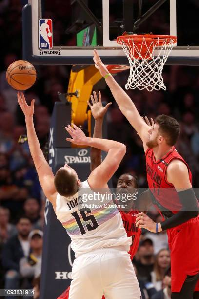 Nikola Jokic of the Denver Nuggets throws up a shot against AlFarouq Aminu and Jusuf Nurkic of the Portland Trail Blazers in the third quarter at the...