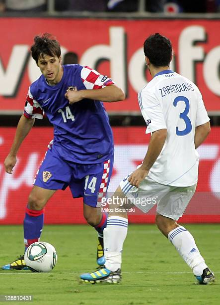 Nikola Kalinic of Croatia dribbles by Giannis Zaradoukas of Greece during the UEFA Euro 2012 Qualifying round group F match between Greece and...