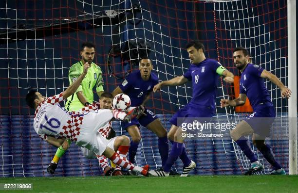 Nikola Kalinic of Croatia try to scores near Sokratis Papastathopoulos of Greece during the FIFA 2018 World Cup Qualifier PlayOff First Leg between...