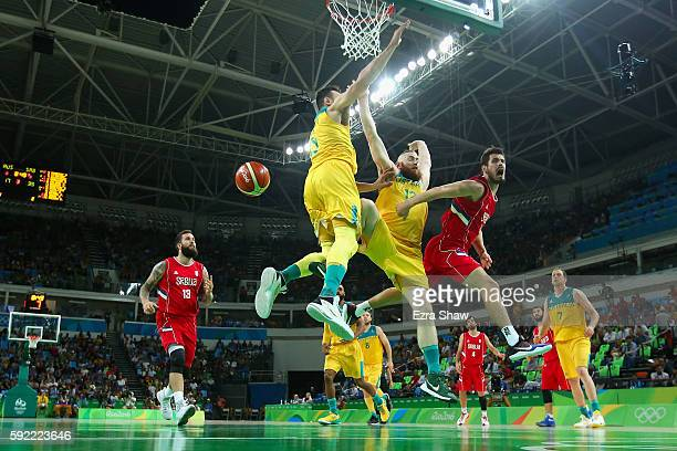 Nikola Kalinic of Serbia makes a leaping pass around Aron Baynes of Australia during the Men's Semifinal match on Day 14 of the Rio 2016 Olympic...