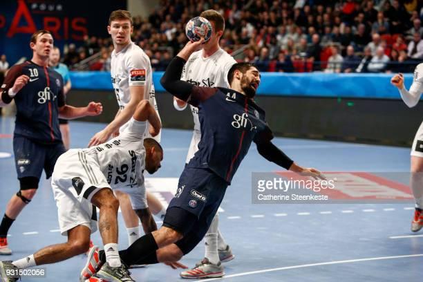 Nikola Karabatic of Paris Saint Germain is shooting the ball against Raul Santos of THW Kiel during the Champions League match between Paris Saint...