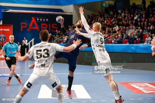 Nikola Karabatic of Paris Saint Germain is shooting the ball against Nikola Bilyk and Sebastian Firnhaber of THW Kiel during the Champions League...