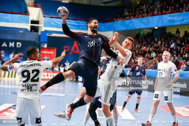 Nikola Karabatic of Paris Saint Germain is shooting the ball against Raul Santos and Nikola Bilyk of THW Kiel during the Champions League match...
