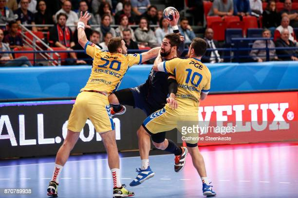 Nikola Karabatic of Paris Saint Germain is trying to shoot the ball against Mariusz Jurkiewicz and Alex Dujshebaev Dovichebaeva of PGE Vive Kielce...