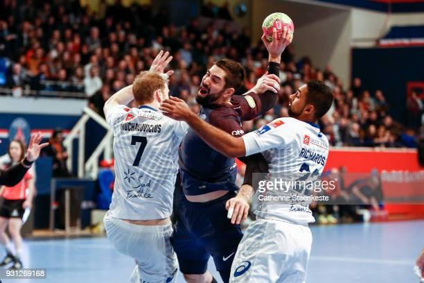 Nikola Karabatic of Paris Saint Germain is trying to shoot the ball against Jonas Truchanovicius of Montpellier Handball and Melvyn Richardson of...