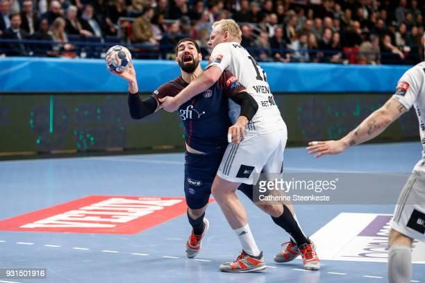 Nikola Karabatic of Paris Saint Germain is trying to shoot the ball against Patrick Wiencek of THW Kiel during the Champions League match between...