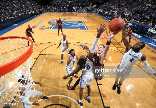 Nikola Maric of the ArkansasLittle Rock Trojans drives to the basket against Kyvon Davenport and Raynere Thornton of the Memphis Tigers on December...