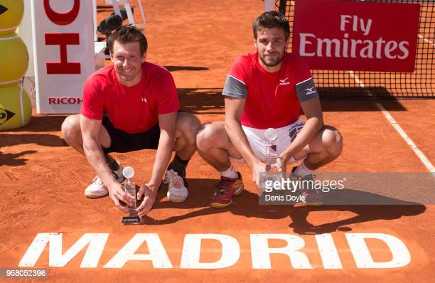 Nikola Mektic of Croatia and Alexander Peya of Austria celebrate with their trophies by the Madrid Open logo after winning the doubles final against...