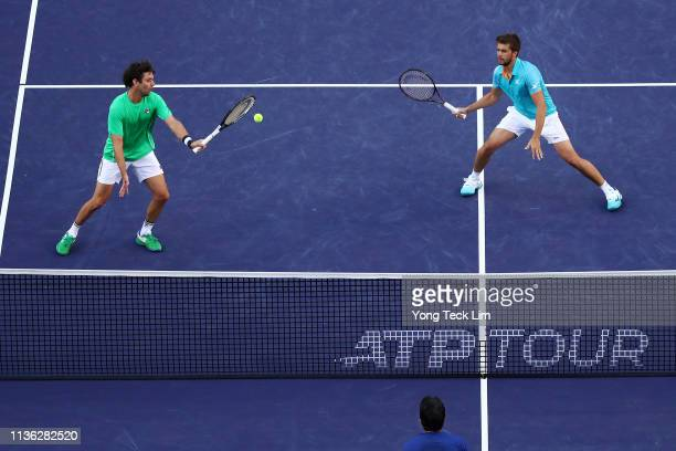 Nikola Mektic of Croatia and Horacio Zeballos of Argentina return the ball against Lukasz Kubot of Poland and Marcelo Melo of Brazil during their...