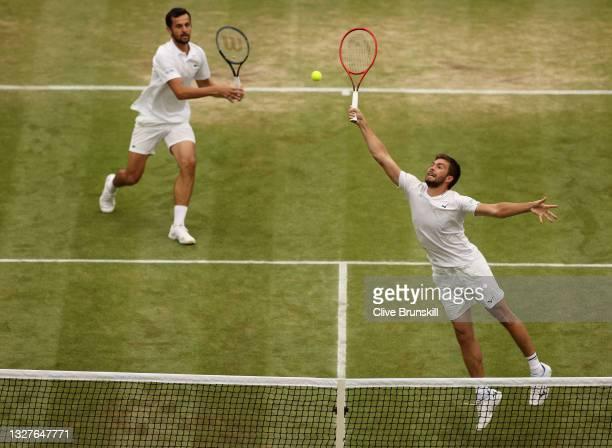 Nikola Mektic of Croatia, playing partner of Mate Pavic of Croatia stretches to play a forehand at the net in their Men's Doubles Semi-Final match...