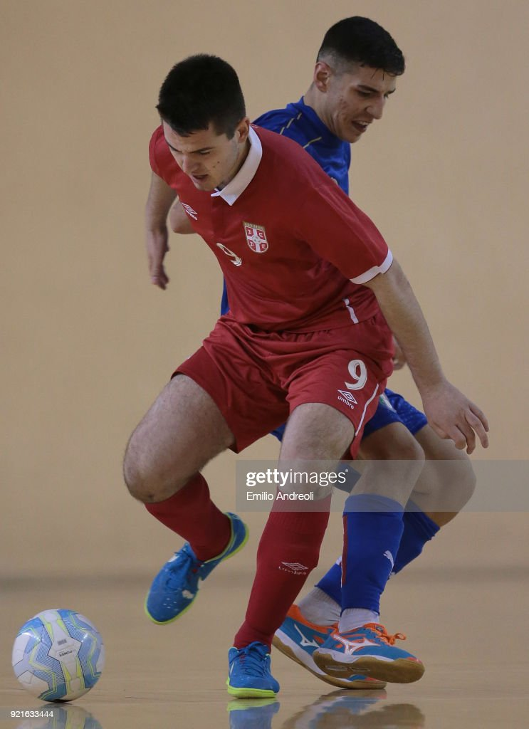 Nikola Milasinovic (front) of Serbia is challenged by Francesco Lo Cicero of Italy during the Futsal International Friendly match between Italy U19 and Serbia U19 at Novarello Training Center on February 20, 2018 in Novara, Italy.