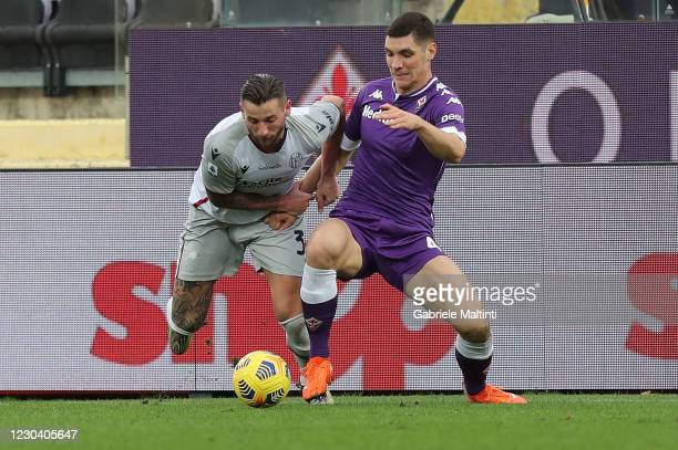 Nikola Milenkovic of ACF Fiorentina battles for the ball with Mitchell Dijks of Bologna FC during the Serie A match between ACF Fiorentina and...