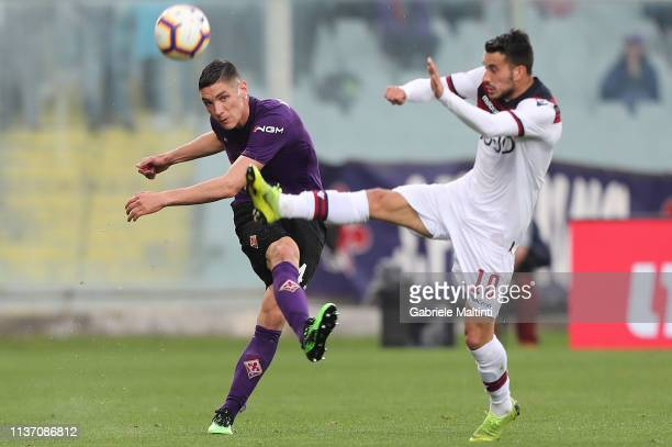Nikola Milenkovic of ACF Fiorentina battles for the ball with Nicola Sansone of Bologna FC during the Serie A match between ACF Fiorentina and...
