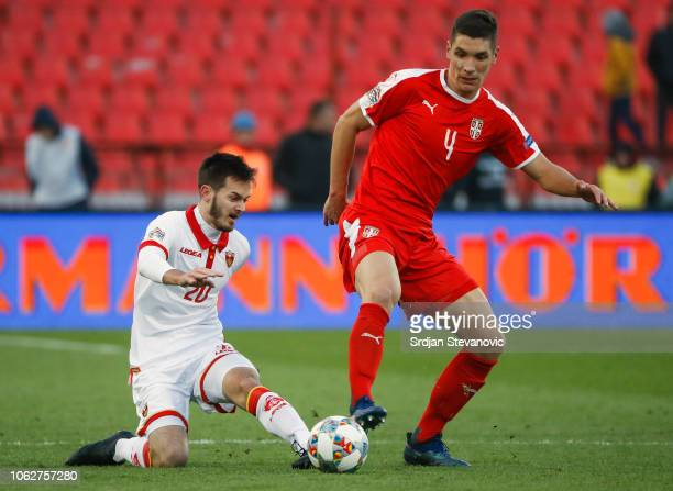 Nikola Milenkovic of Serbia compestes for the ball against Marko Ivanic of Montenegro during the UEFA Nations League C group four match between...