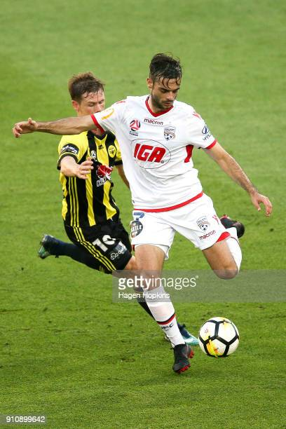 Nikola Mileusnic of Adelaide United beats the challenge of Michael McGlinchey of the Phoenix during the round 18 ALeague match between the Wellington...