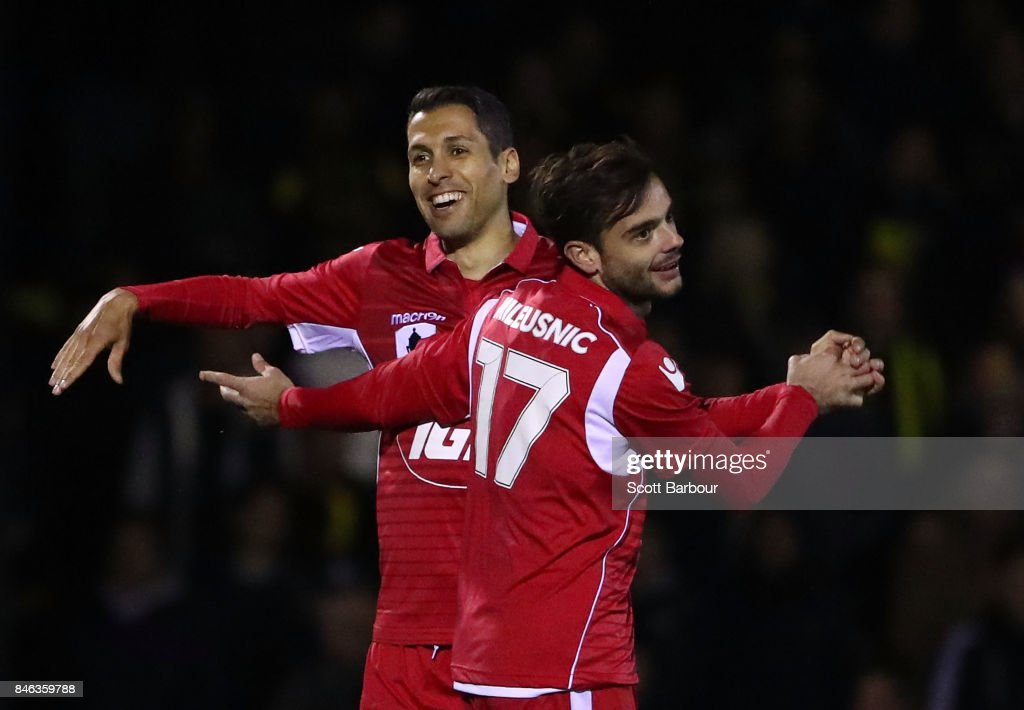 Nikola Mileusnic of Adelaide United is congratulated by Karim Matmour after scoring a goal during the FFA Cup Quarter Final match between Heidelberg United FC and Adelaide United at Olympic Village on September 13, 2017 in Melbourne, Australia.