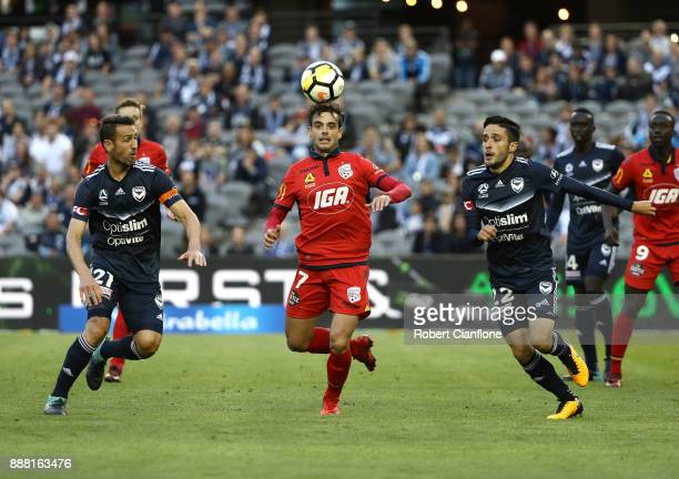 Nikola Mileusnic of Adelaide United is pressured by Carl Valeri and Stefan Nigro of the Victory during the round 10 ALeague match between the...