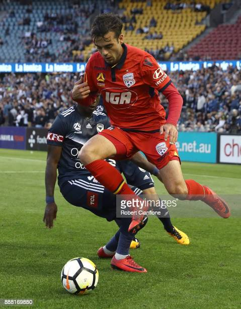 Nikola Mileusnic of Adelaide United leaps over a challenge from Leroy George of the Victory during the round 10 ALeague match between the Melbourne...