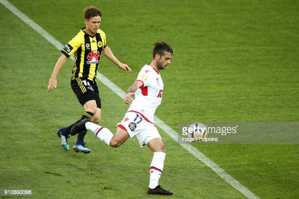 Nikola Mileusnic of Adelaide United looks to pass under pressure from Michael McGlinchey of the Phoenix during the round 18 ALeague match between the...