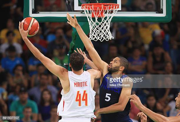 Nikola Mirotic of Spain goes to the basket against Nicolas Batum of France during the Men's Quarterfinal match on Day 12 of the Rio 2016 Olympic...