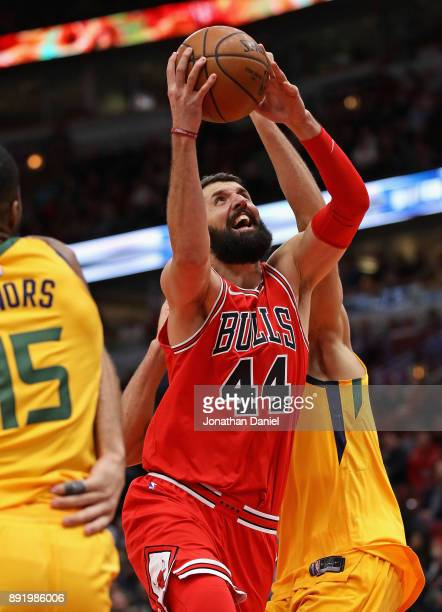 Nikola Mirotic of the Chicago Bulls drives between Derrick Favors and Rudy Gobert of the Utah Jazz at the United Center on December 13 2017 in...
