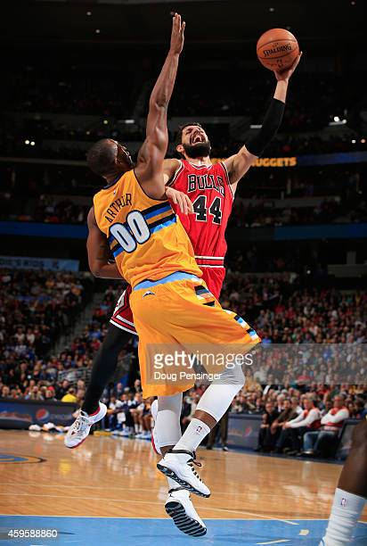 Nikola Mirotic of the Chicago Bulls goes to the basket and is fouled by Darrell Arthur of the Denver Nuggets at Pepsi Center on November 25 2014 in...
