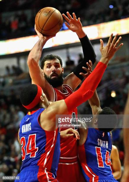 Nikola Mirotic of the Chicago Bulls leaps to pass over Tobias Harris and Ish Smith of the Detroit Pistons at the United Center on March 22, 2017 in...