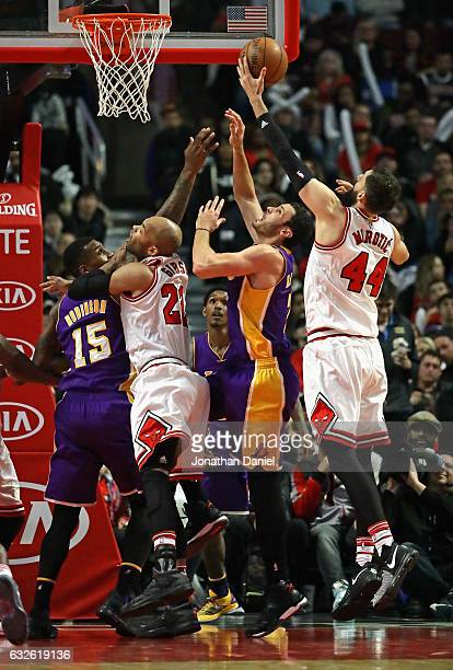 Nikola Mirotic of the Chicago Bulls rebounds over Larry Nance Jr #7 and Thomas Robinson of the Los Angeles Lakers and teammate Taj Gibson at the...