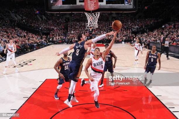 Nikola Mirotic of the New Orleans Pelicans reaches to block as CJ McCollum of the Portland Trail Blazers shoots a layup during the game between the...