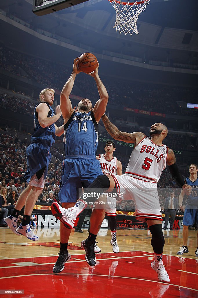 Nikola Pekovic #14 of the Minnesota Timberwolves grabs a rebound over Carlos Boozer #5 of the Chicago Bulls on November 10, 2012 at the United Center in Chicago, Illinois.