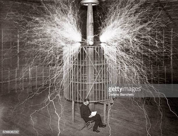 """Nikola Tesla , Serbian-American physicist sitting in his Colorado Springs laboratory with his """"Magnifying transmitter"""" - 1899"""